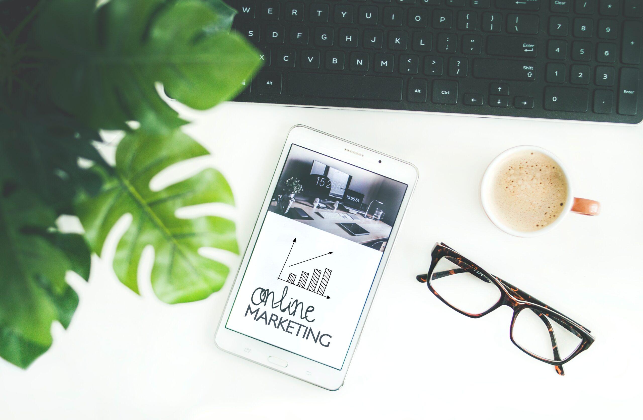 scrivania bianca per marketing e web marketing vista dall'alto con tablet, tastiera, occhiali e tazzina di caffè